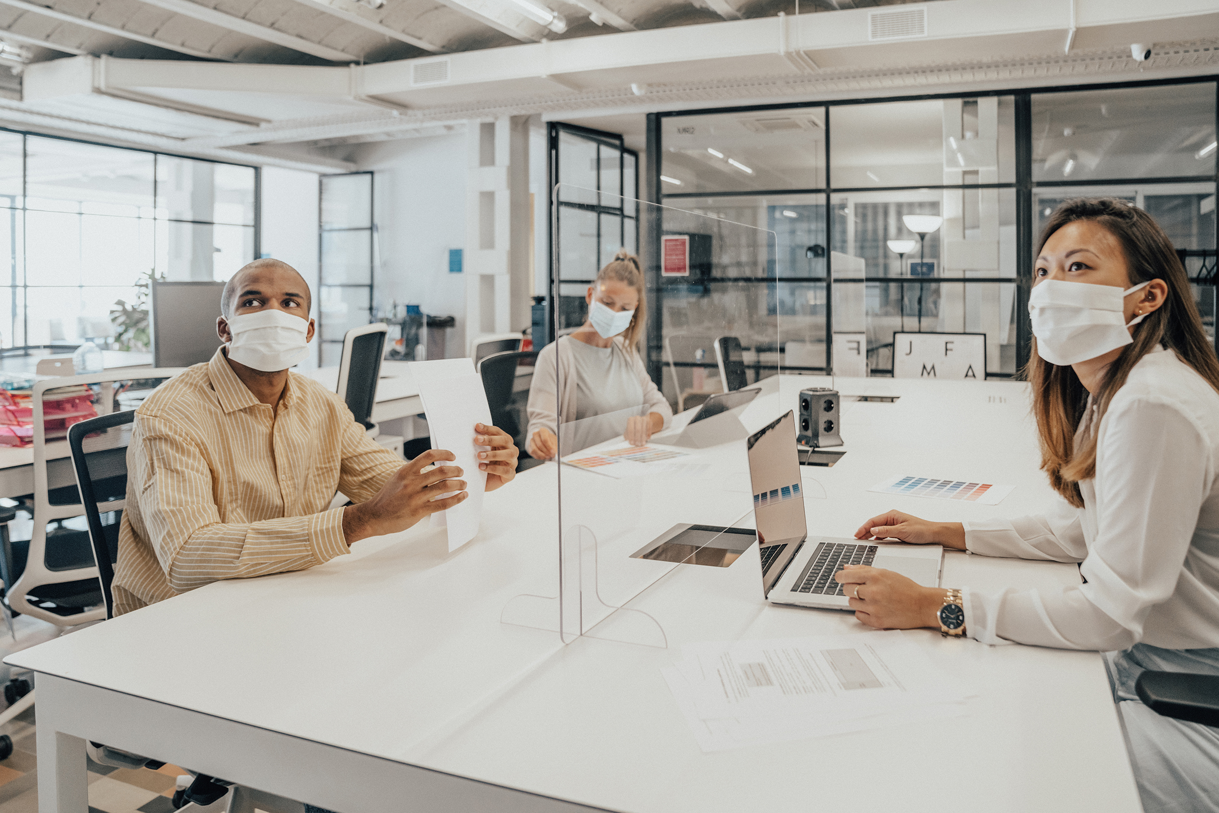 Businesspeople working at office with glass partition dividing them